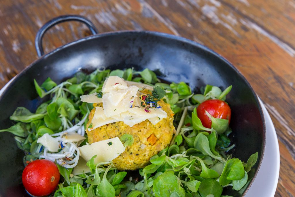 Close-up of pumpkin Knödel (dumpling) in a pan with salad and parmesan cheese slices in Alpbach