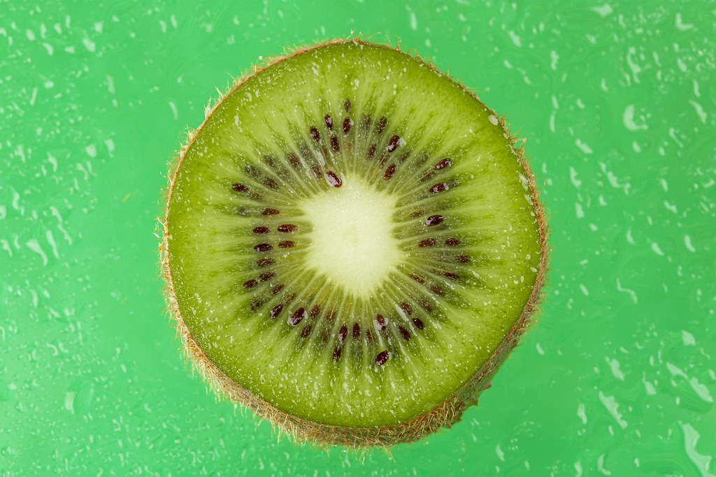 Close-up of sliced kiwi on green background with water drops