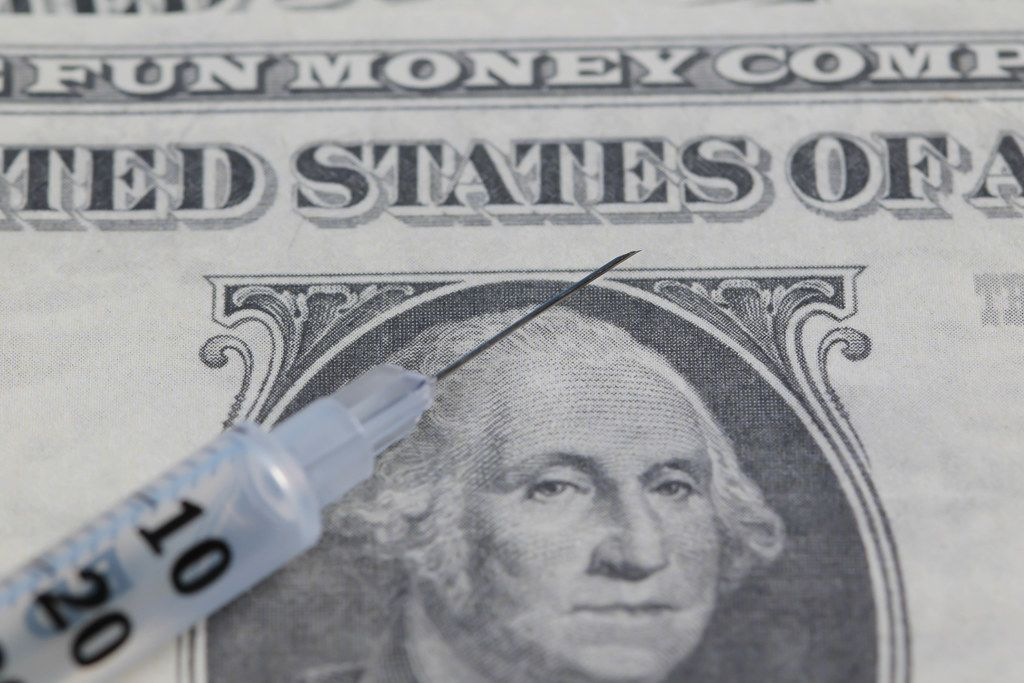 Close up of syringe with money