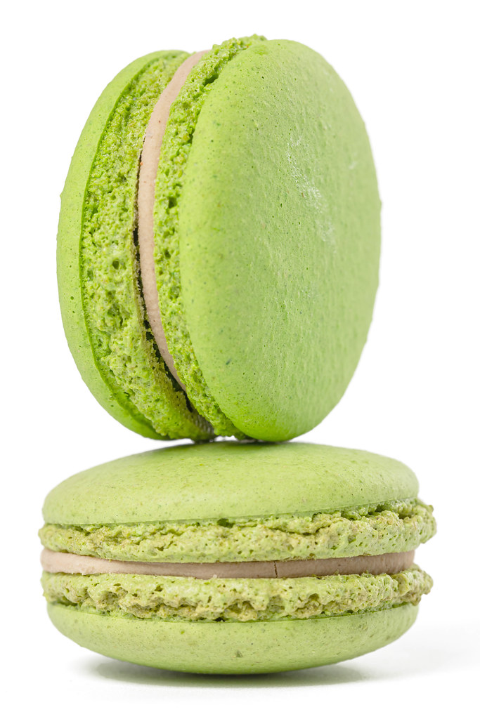 Close-up of two green macaroons on white