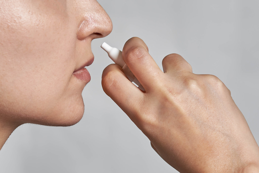 Close-up of unrecognizable woman using nasal spray