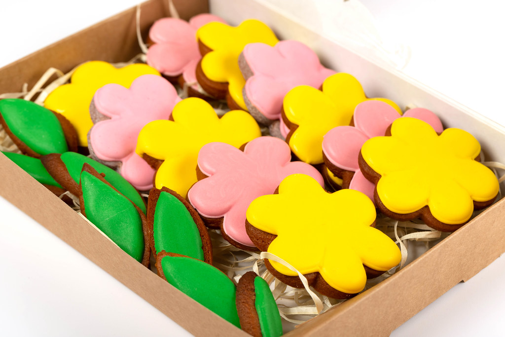 Close-up of yellow and pink gingerbread flowers and green leaves in a cardboard box