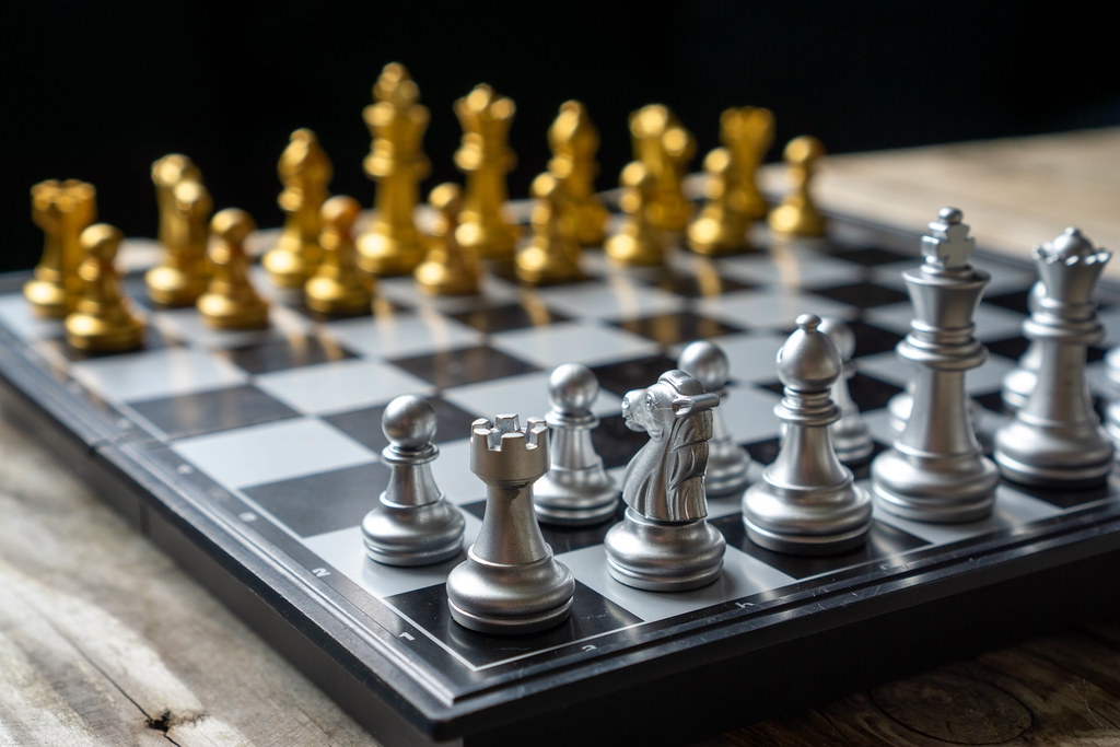 Close Up Photo of a Foldable Travle Chess Board with Silver and Golden Chess Pieces in Starting Position on a Wooden Table