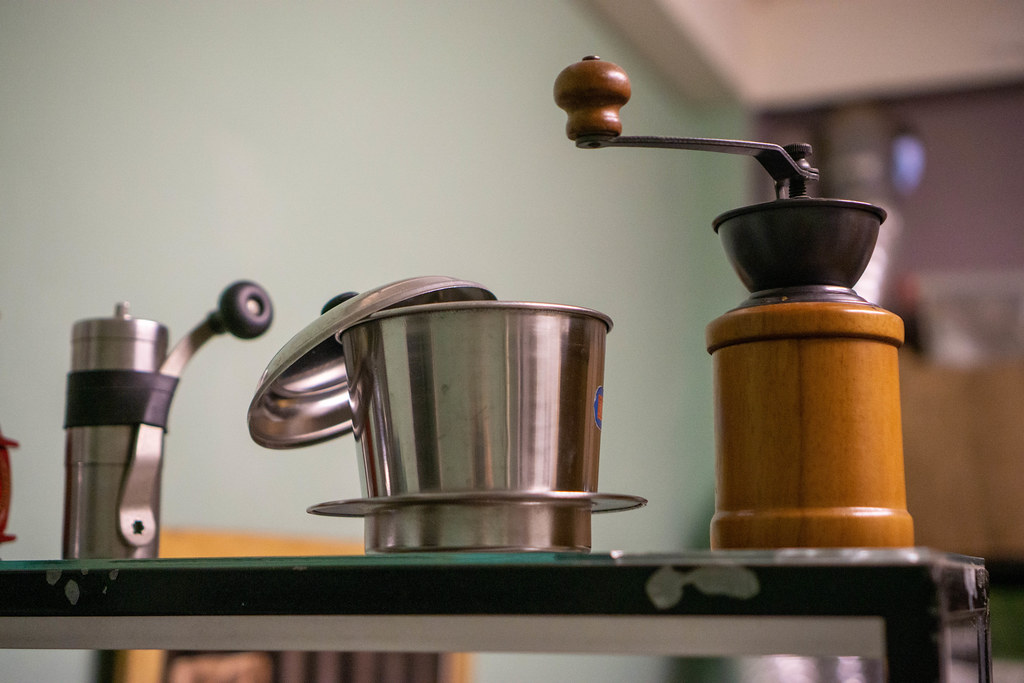 Close Up Photo of Hand Coffee Grinder and a Vietnamese Coffee Filter on a Shelf in a Cafe