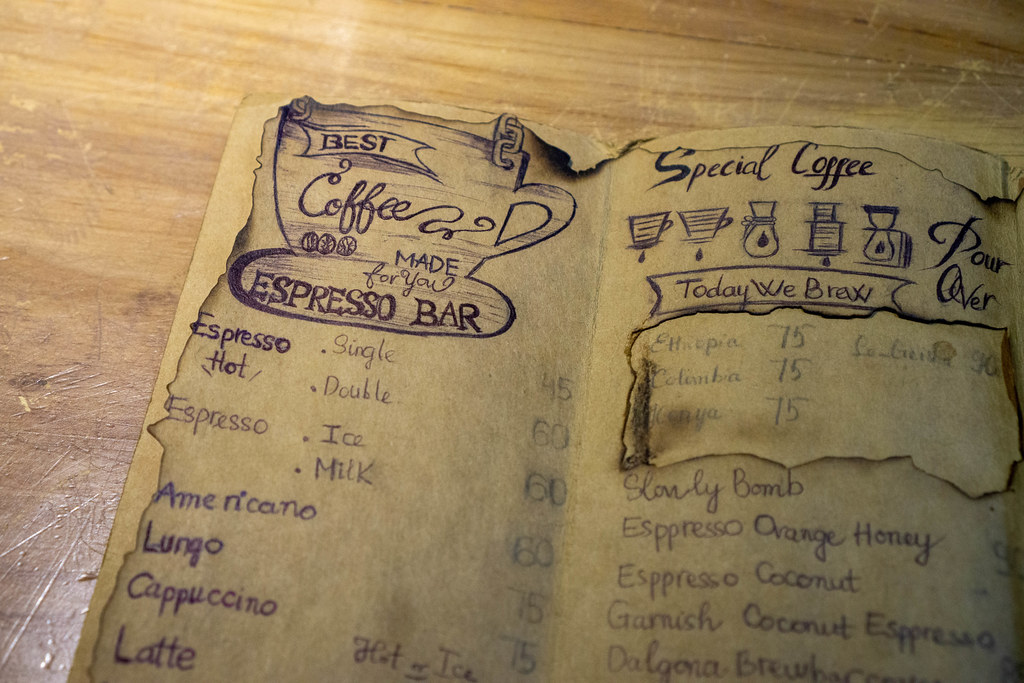 Close Up Photo of Hand Written Vintage Menu with Drawings and different Drinks on a Wooden Table in a Cafe