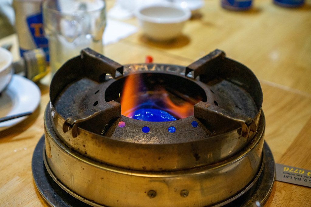Close Up Photo of Hot Pot Stove with Burning Gel Wax on a Wooden Table in a Restaurant