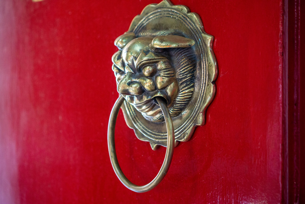 Close Up Photo of Metal Door Knocker in Shape of a Chinese Guardian Lion with Large Ring on a Red Wooden Door of Phuc Kien Pagoda in Hoi An, Vietnam
