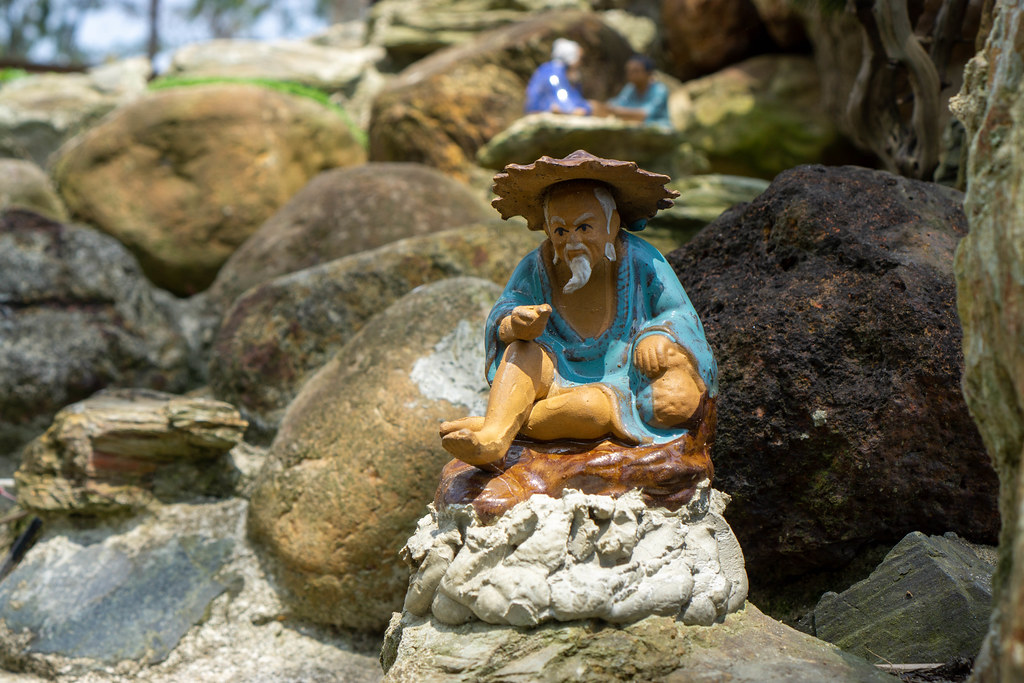 Close Up Photo of Painted Miniature Figure of an Asian Old Man sitting on a Rock in the Garden of Sound of Silence Coffee at An Bang Beach in Hoi An, Vietnam