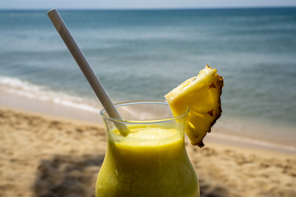 Close Up Photo of Pina Colada with Fresh Pineapple and Paper Drinking Straw in a Cocktail Glass with Beach and Sea in the Background
