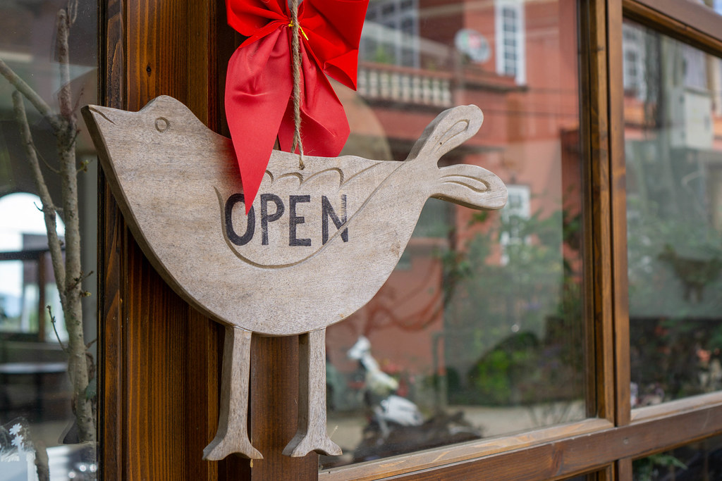 Close Up Photo of Wooden Open Sign Board in Bird Shape on a Door of a Cafe