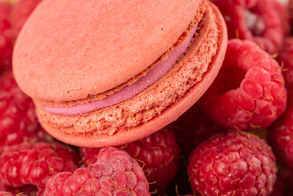 Close-up, pink macaroons on the background of raspberries