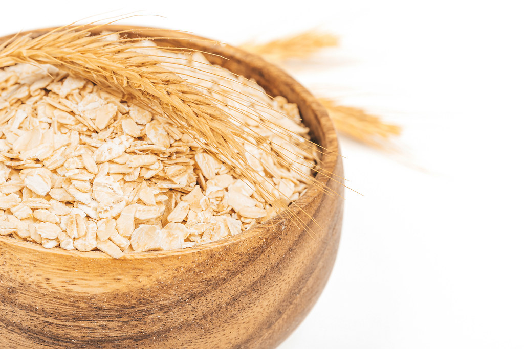 Close-up, raw oatmeal in a wooden bowl and spikelets