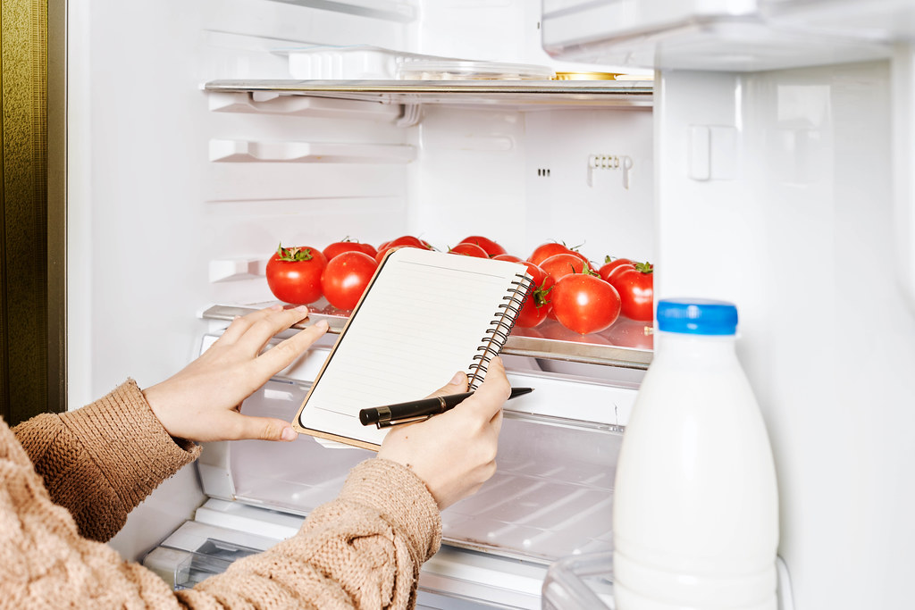 Close-up shot of female checking products in the fridge and making a shopping list