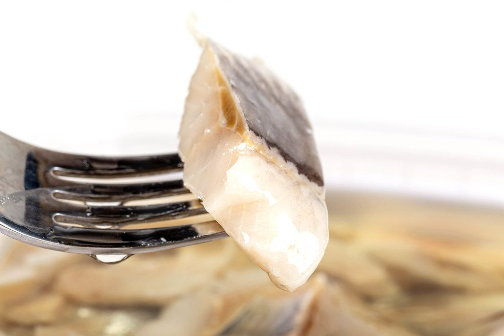 Close-up, slice of pickled herring on a fork