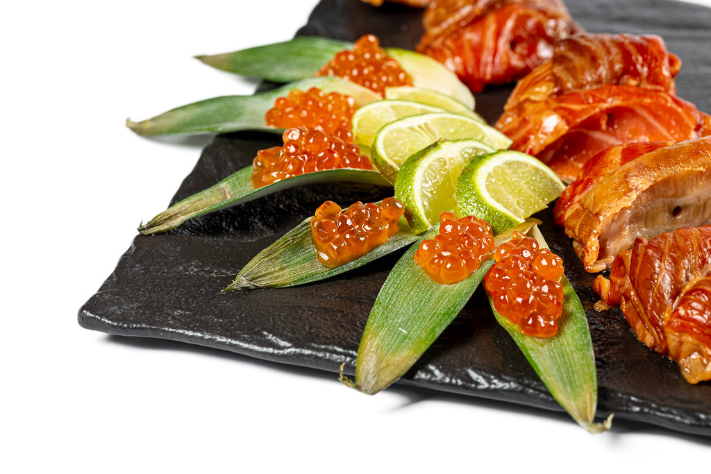 Close-up, smoked salmon fillet with red caviar and lime