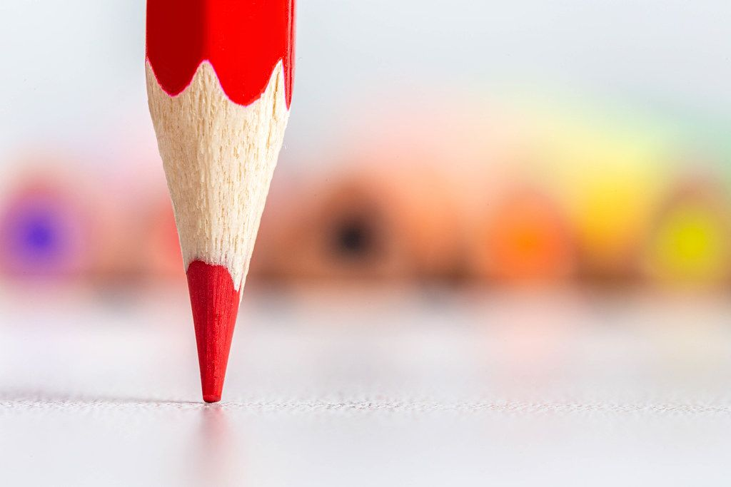 Close-up, tip of red pencil with colored pencils behind