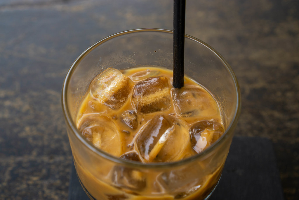 Close Up Top View Photo of Vietnamese Iced Coffee with Sweetened Condensed Milk in a Glass with Plastic Drinking Straw on a Wooden Table