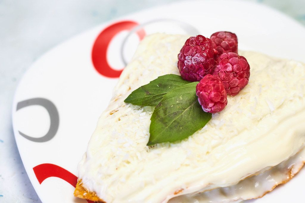Close-up view of carrot cake with cream and fresh raspberries on it
