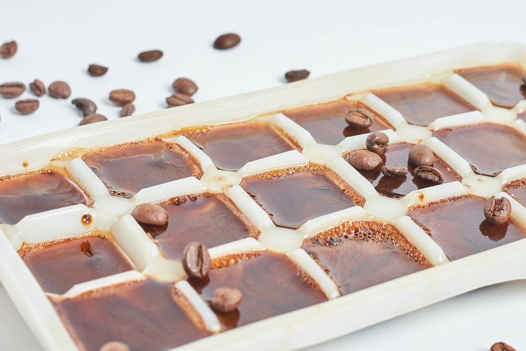 Close-up view of iced coffee cubes and beans