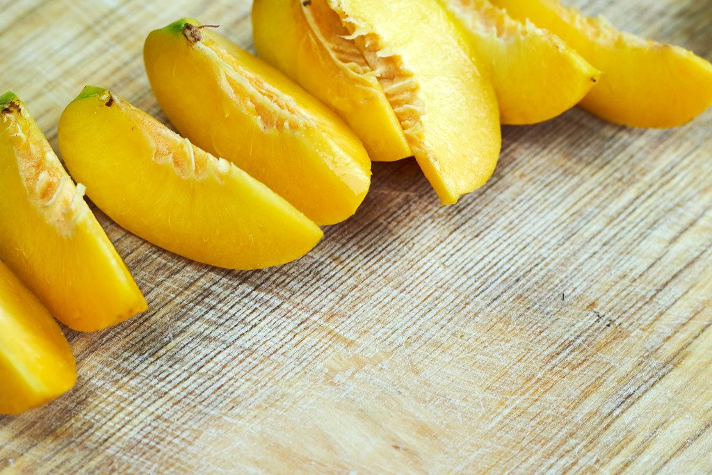 Close-up view of sliced ripe juicy peaches on cutting board