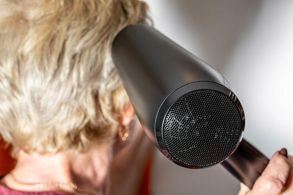 Close up, woman dries hair black hairdryer