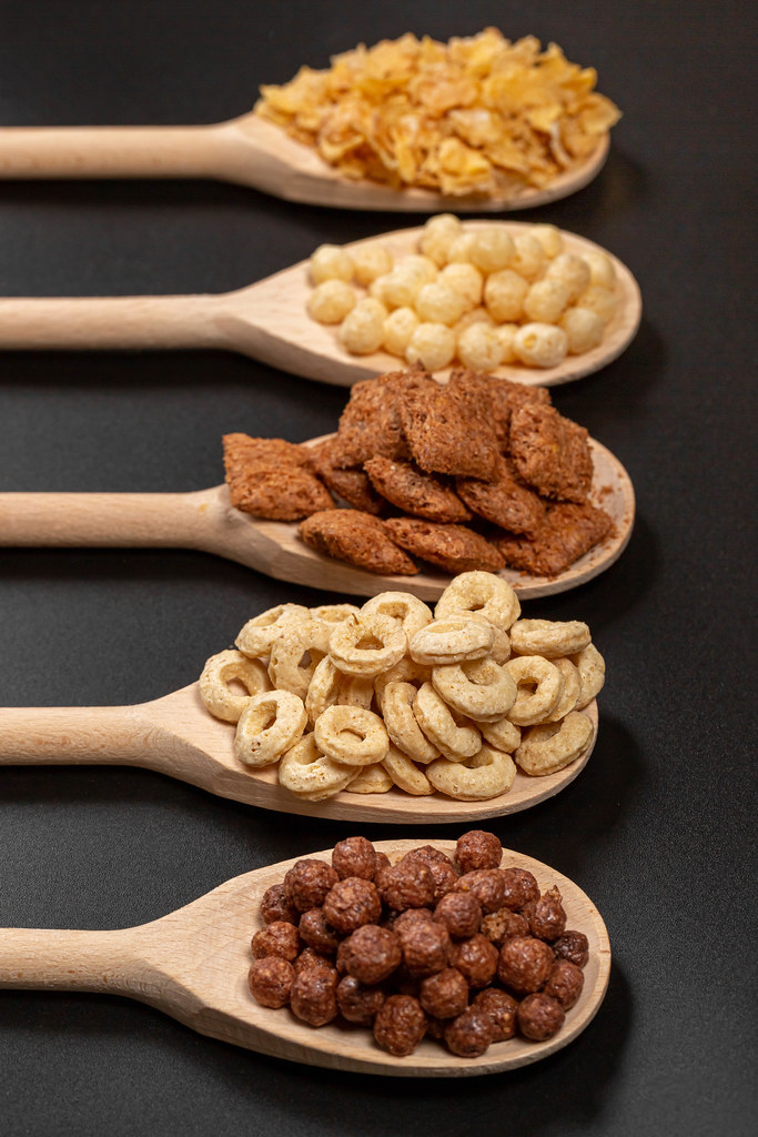 Close-up, wooden spoons with breakfast cereals on a dark background