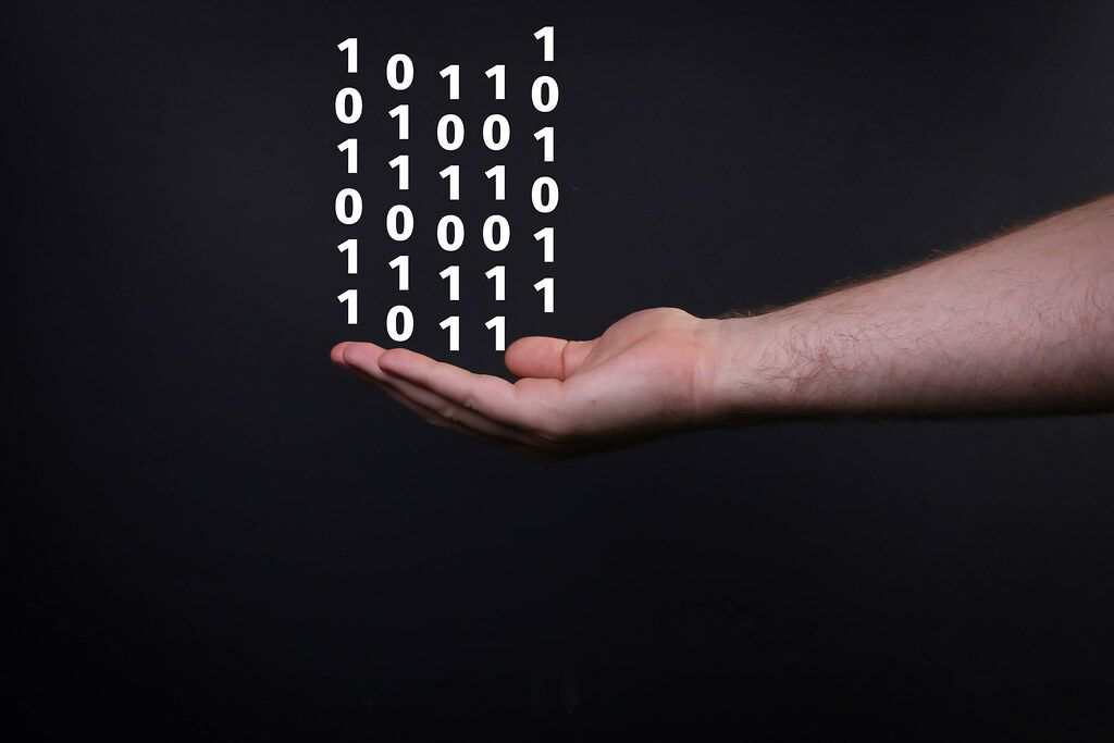 Closeup shot of male hand and binary code isolated on black background