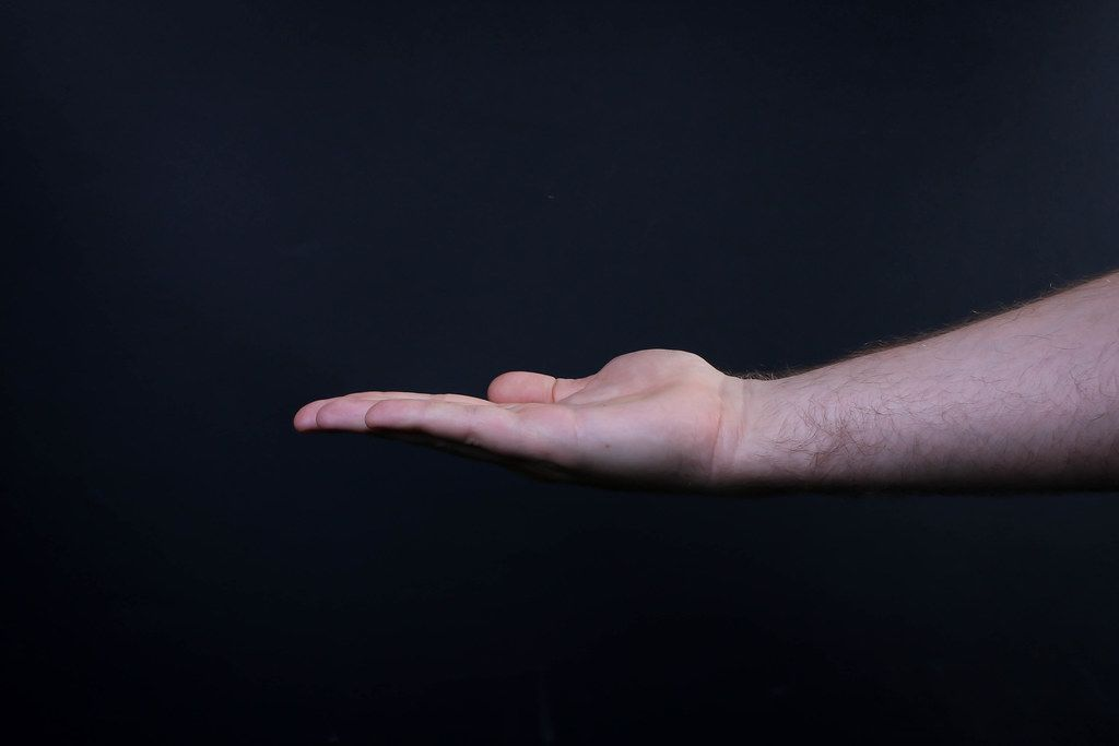 Closeup shot of male hand isolated on black background