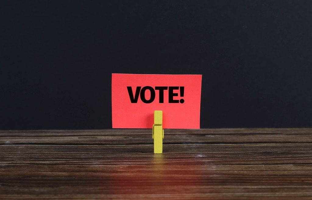 Clothespin holding red paper with Vote text