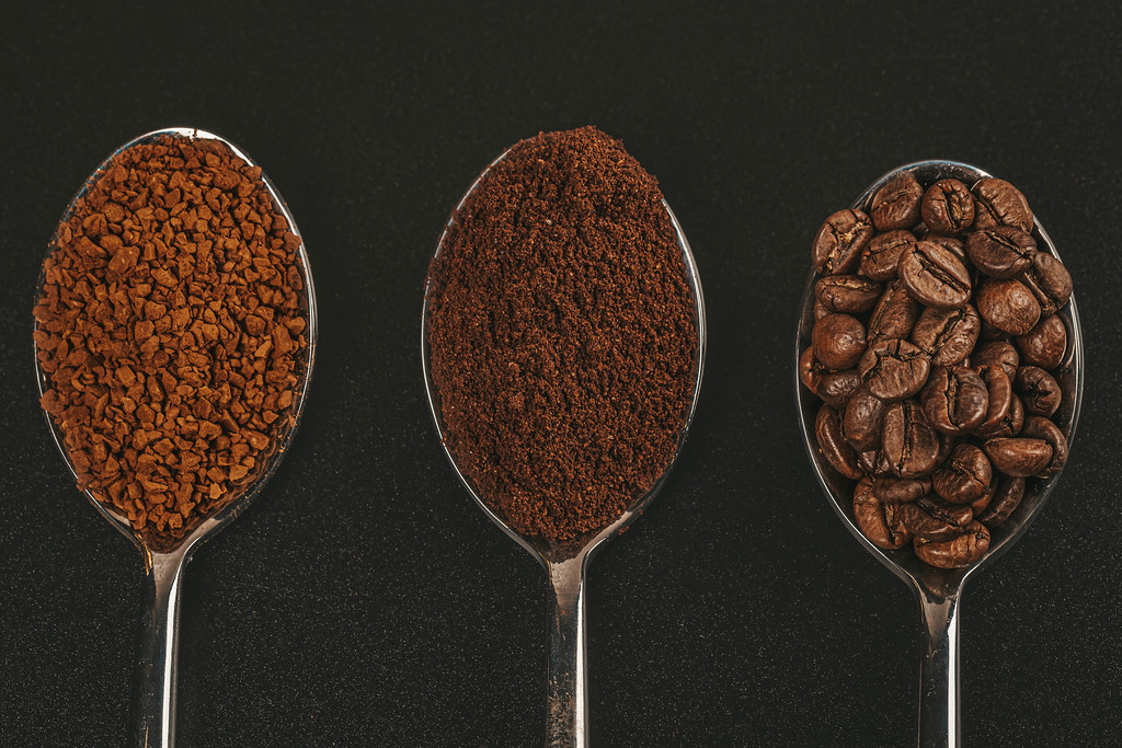 Coffee beans, ground and instant coffee granules in spoons, top view