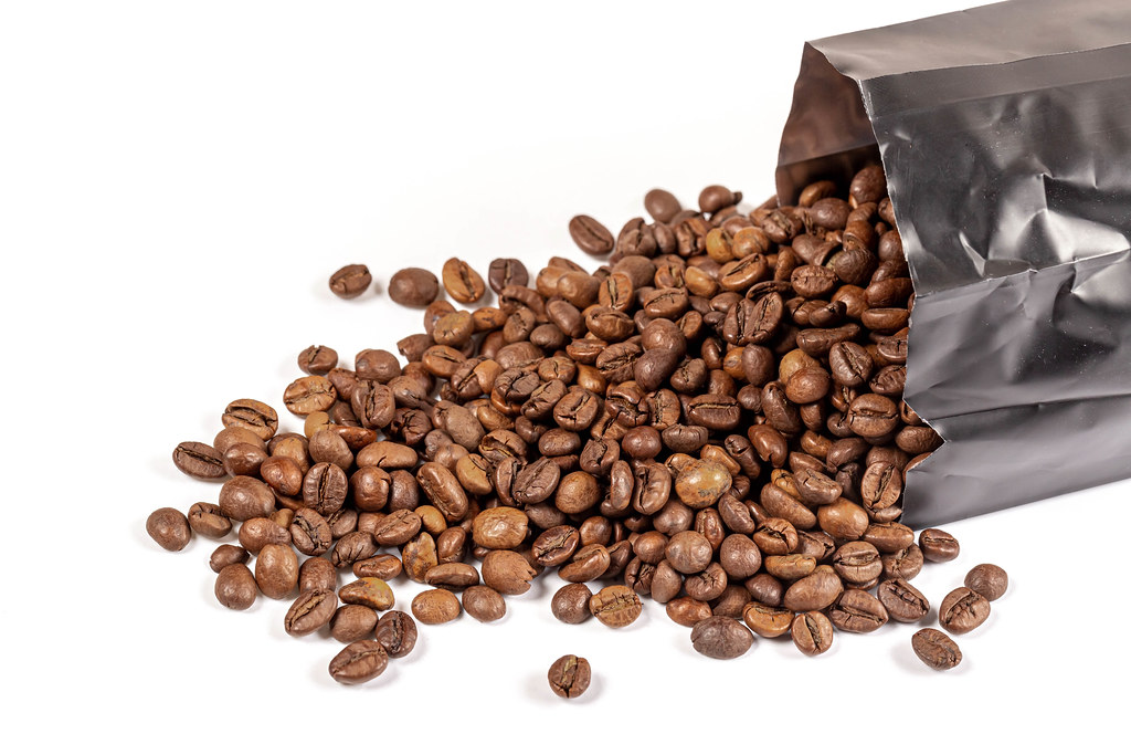 Coffee beans scattered from the packaging on white