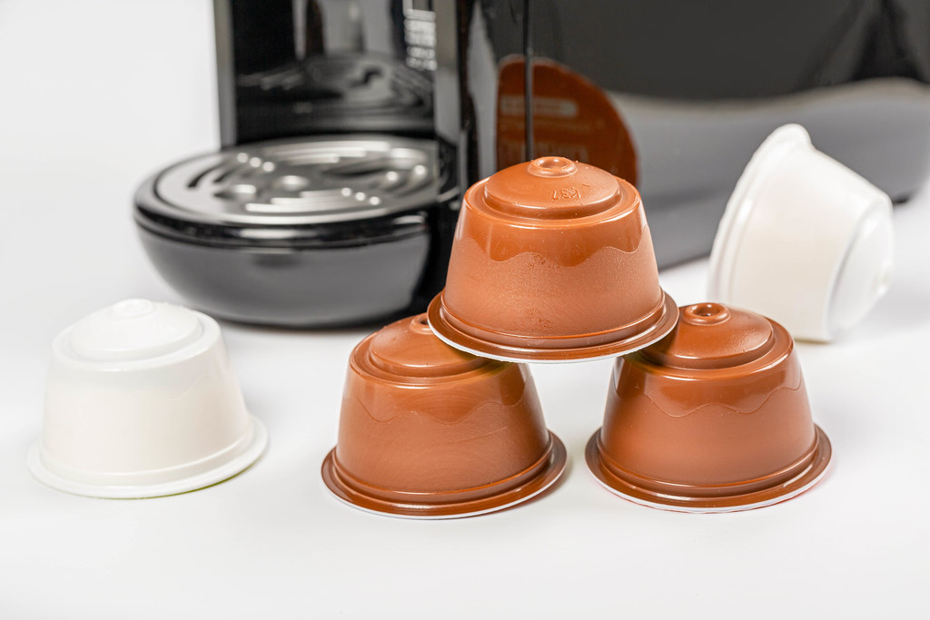 Coffee capsules on white background with coffee maker behind