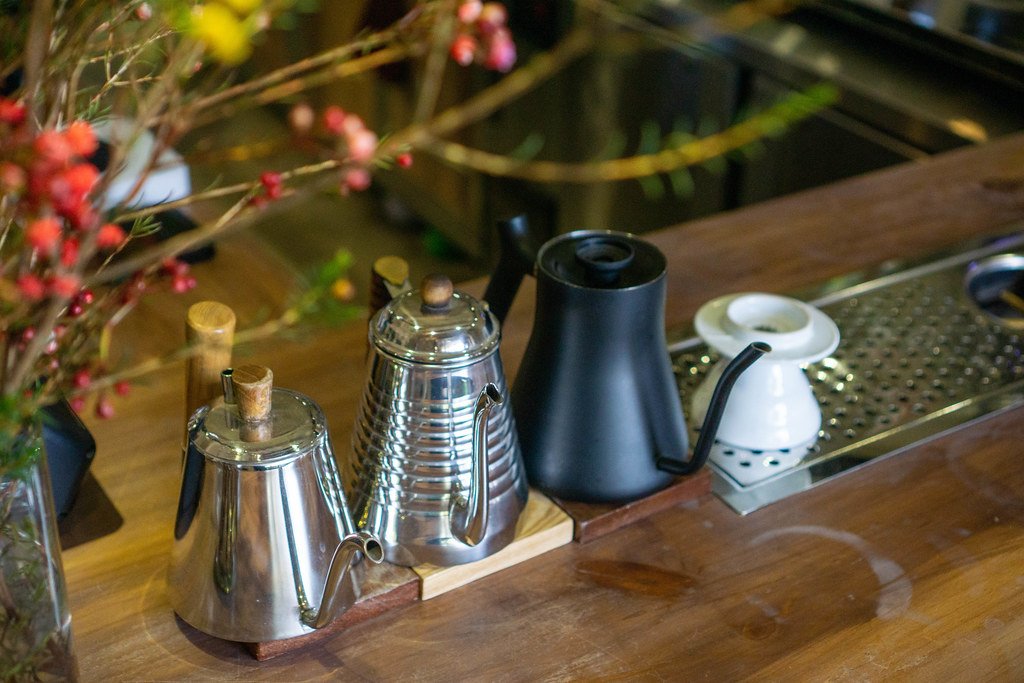 Coffee Pour Over Gooseneck Kettles in different Designs on a Wooden Countertop of a Bar Style Cafe