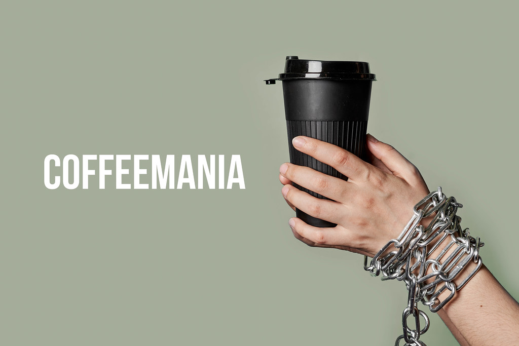 Coffeemania concept with chained person hands holding a cup of coffee