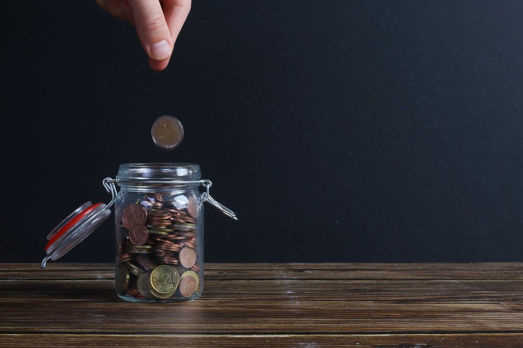 Coin falling into money jar