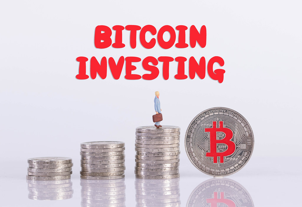 Coin stacks with miniature businessman, silver Bitcoin coin and Bitcoin Investing text