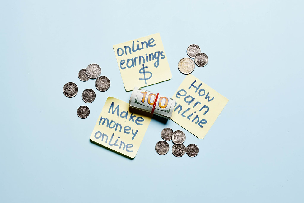Coins, rolled us dollars cash and sticky notes with online earning text