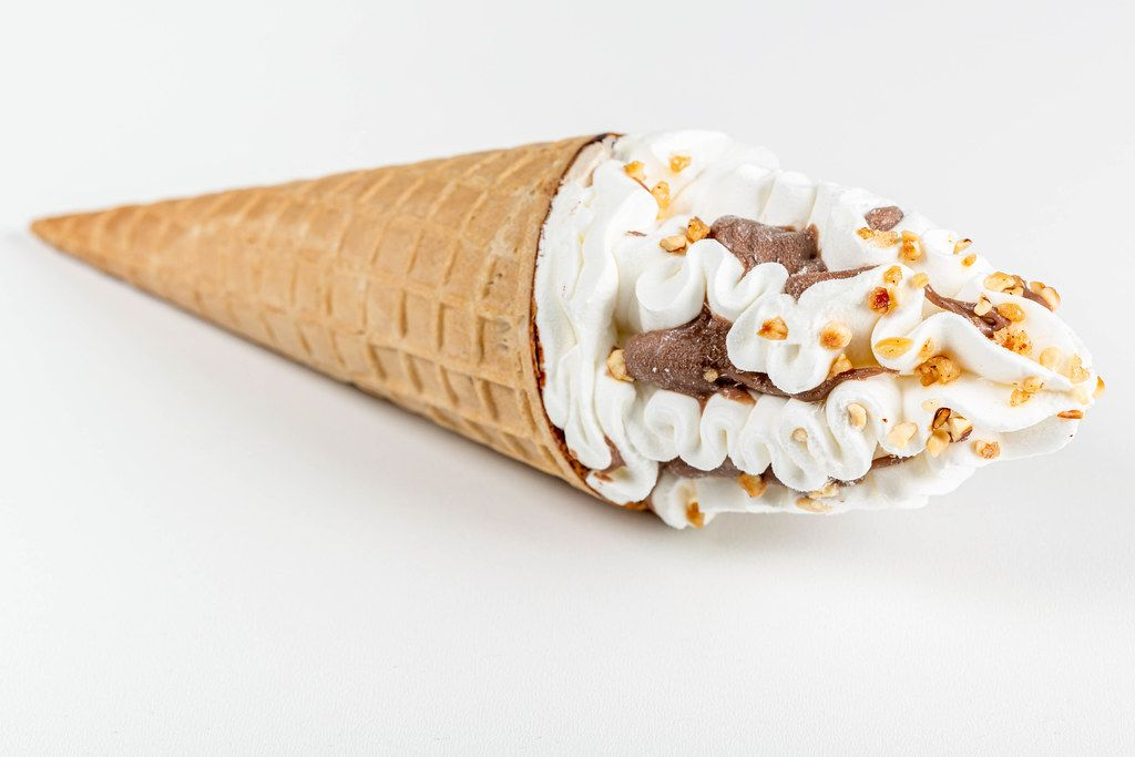 Cold ice cream with chocolate and nuts in a waffle cone on a white background