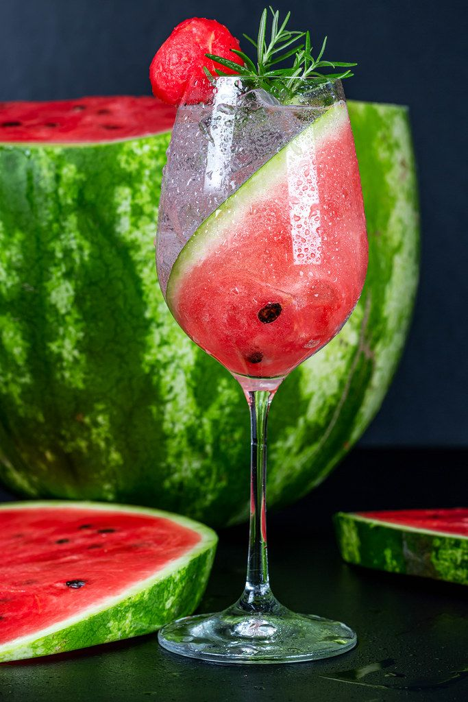 Cold summer cocktail with fresh watermelon and rosemary on a black background