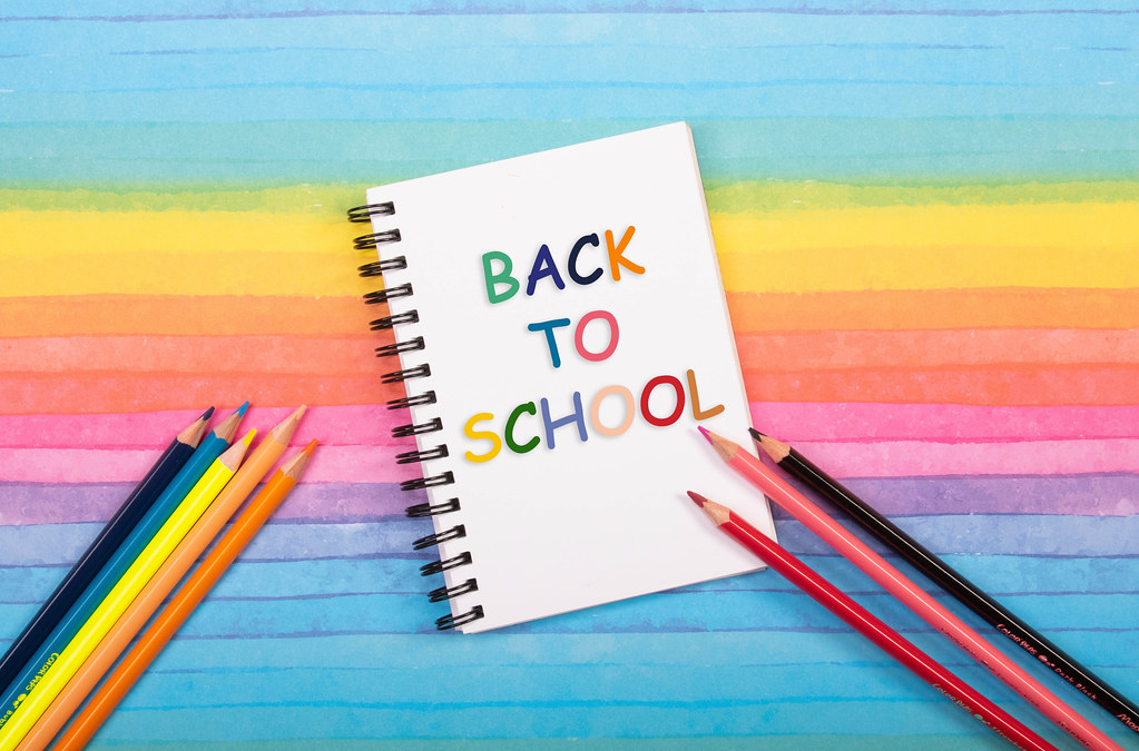Colored pencils and notebook with back to School text on colorful background