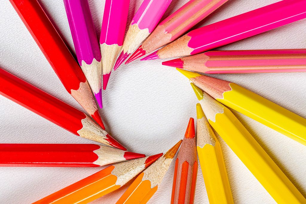 Colored pencils laid out in a circle on a white background