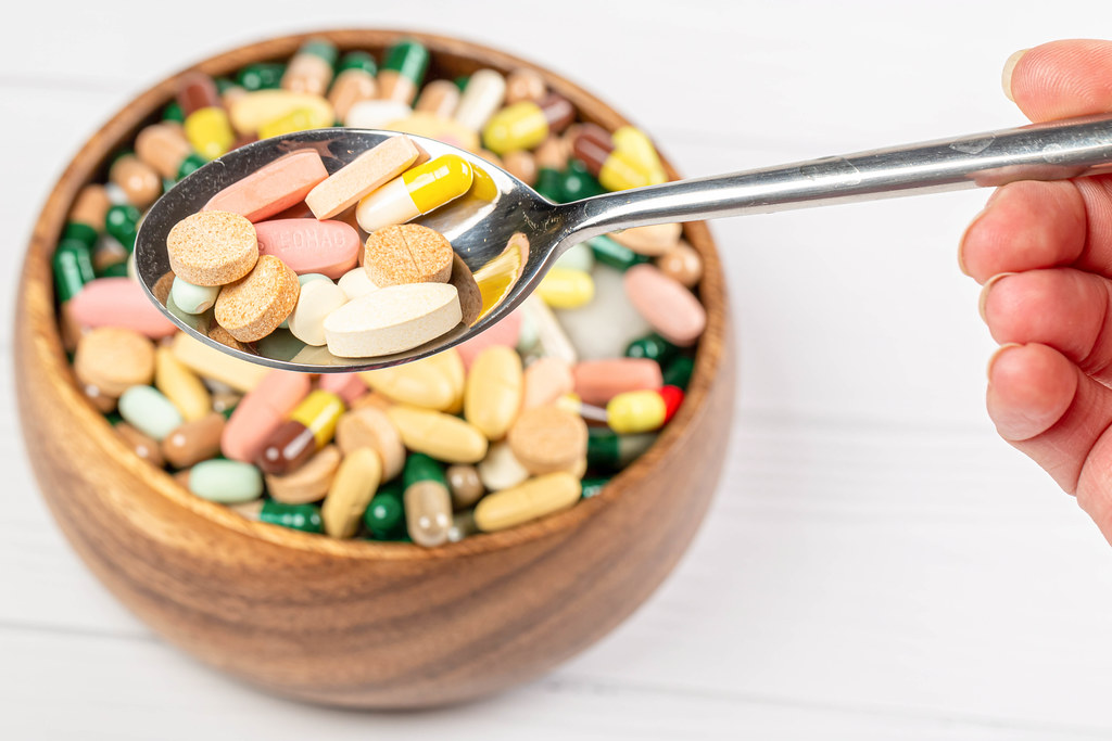 Colorful capsules and tablets in a spoon, close-up