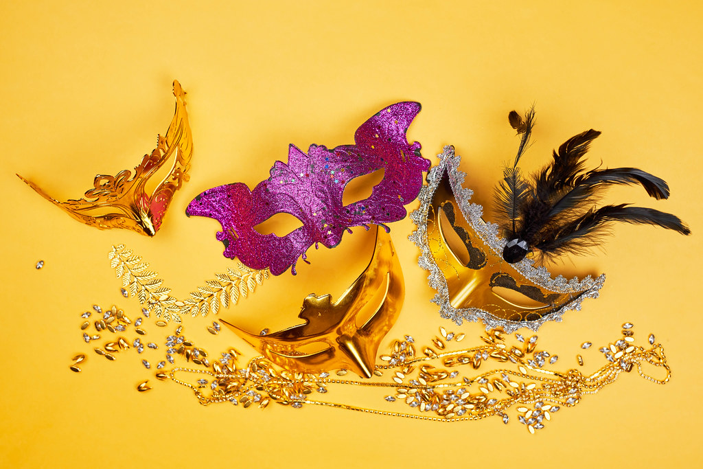 Colorful Mardi Gras masks on yellow background