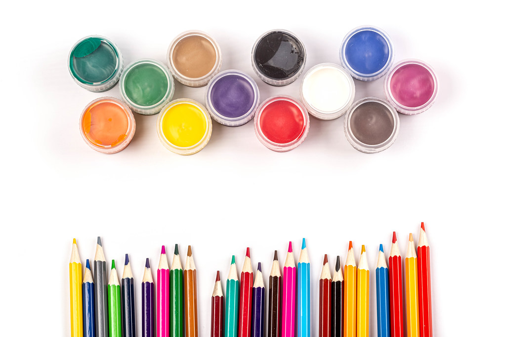 Colorful paints and colored pencils on a white background, top view