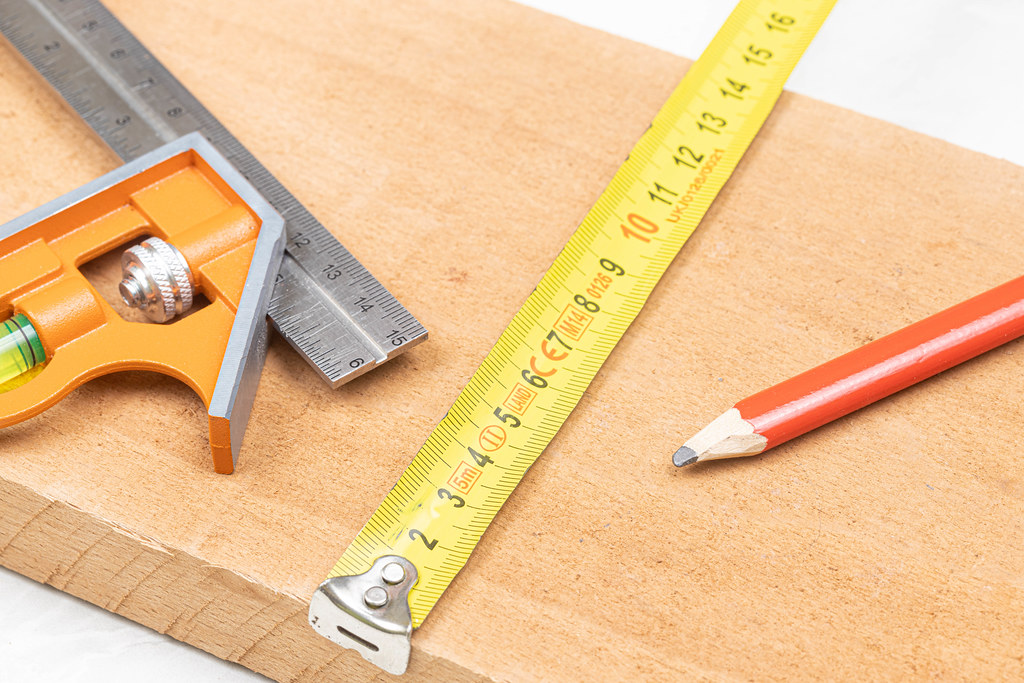 Combination square with wooden pencil and measuring tape on the wooden board