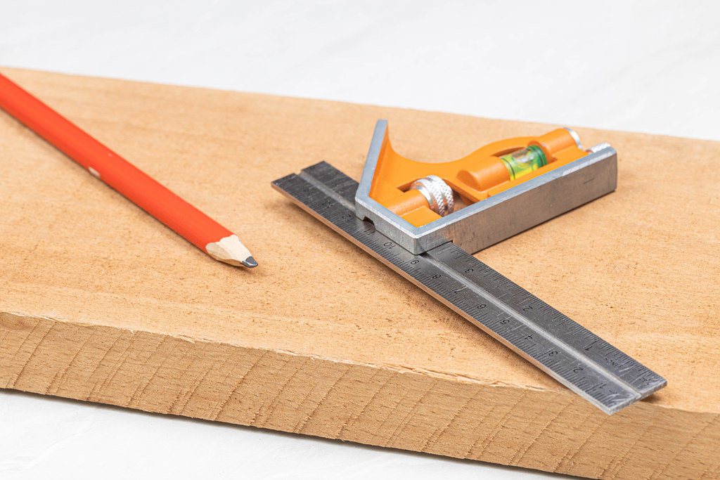 Combination square with wooden pencil on the wooden board