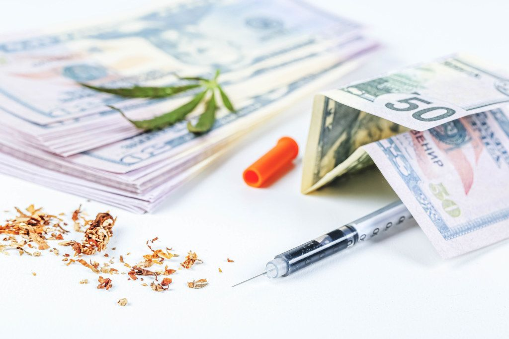 Concept of illegal business and drug problem - syringe, money and cannabis