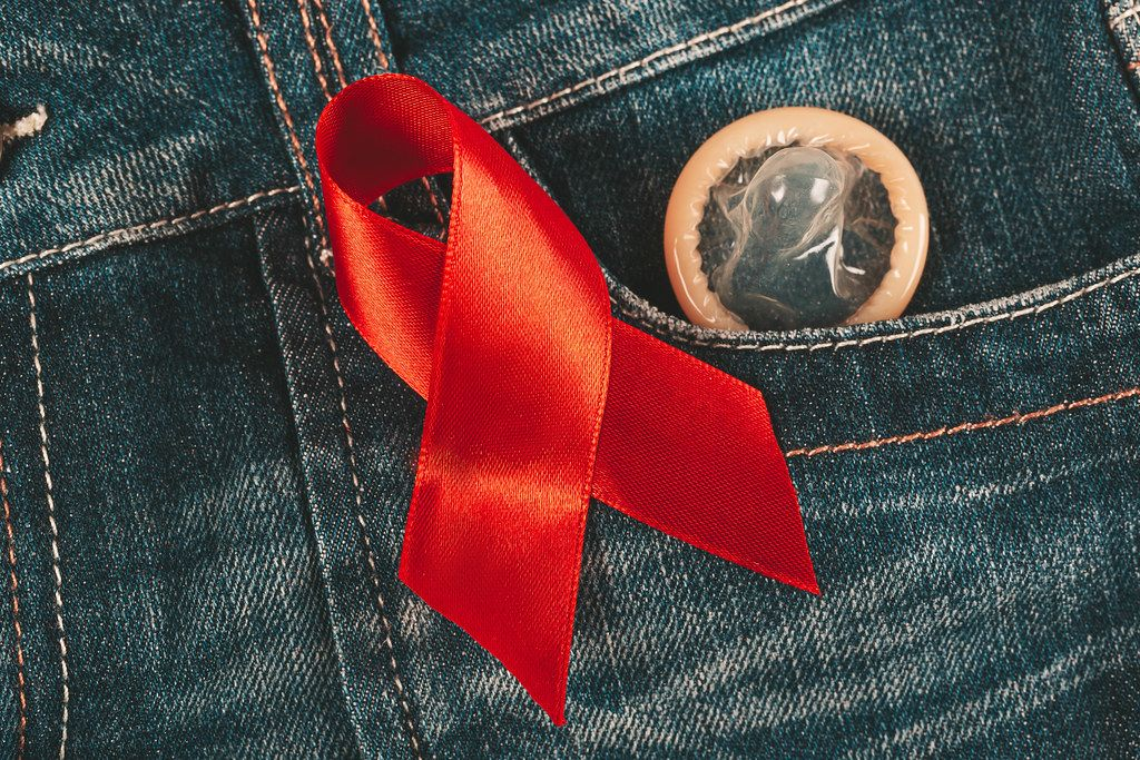 Condom peeking out from jeans pocket with red awareness ribbon for aids and hiv