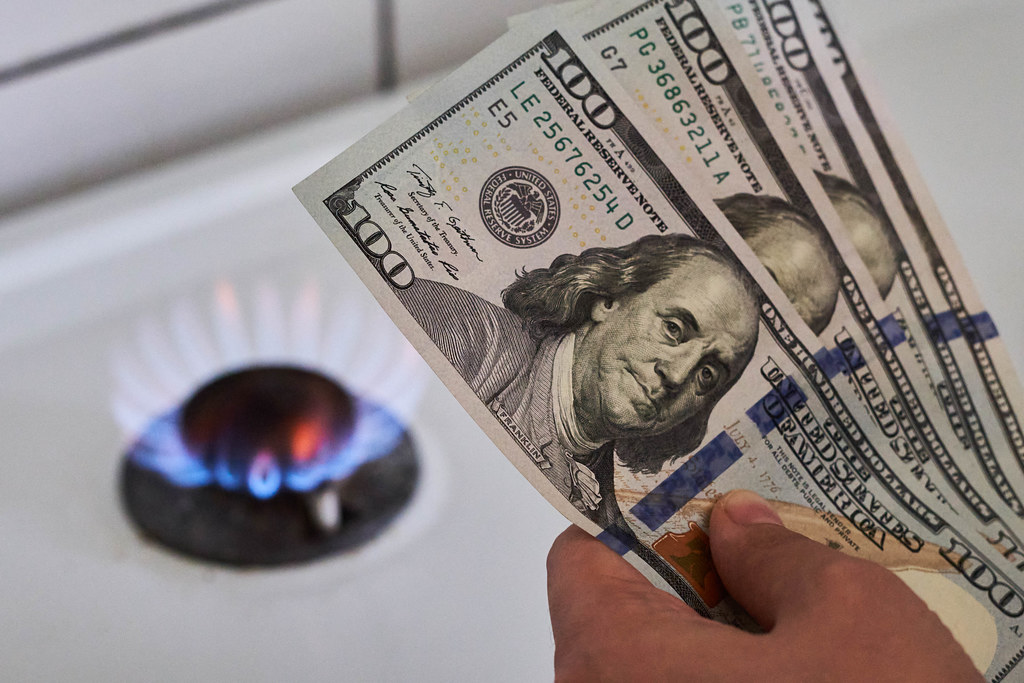 Cooktop with burning gas ring and hand of person holding pile of us dollars