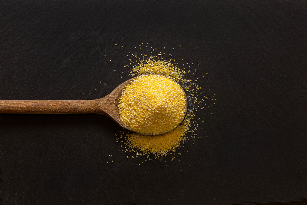 Corn Flour on the wooden spoon with dark background and copy space